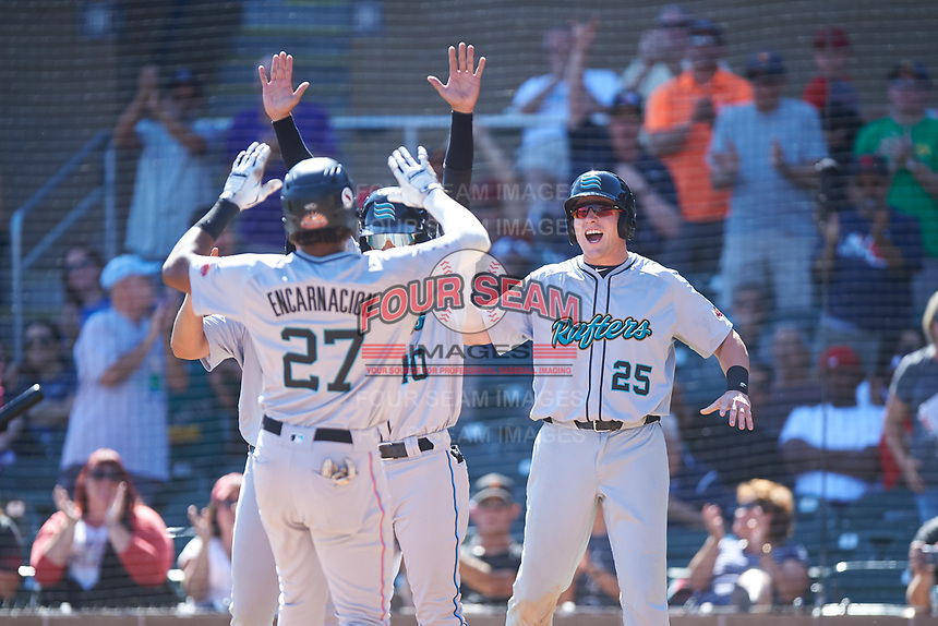 Salt River Rafters Jerar Encarnacion (27), of the Miami Marlins organization, is congratulated by Victor Victor Mesa (10) and Luke Raley (25) after hitting a grand slam during the Arizona Fall League Championship Game against the Surprise Saguaros on October 26, 2019 at Salt River Fields at Talking Stick in Scottsdale, Arizona. The Rafters defeated the Saguaros 5-1. (Zachary Lucy/Four Seam Images)