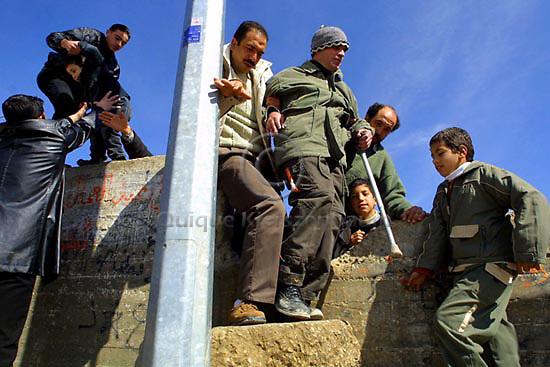 Palestinians help a handicap man to cross a road block in the West Bank neighborhood of Abu Dis, next to Jerusalem, February 11, 2003.  Photo by Quique Kierszenbaum