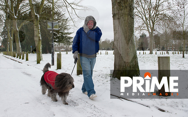 A man walks his dog in the park in Sidcup following Heavy Snowfall at Sidcup, Kent, England on the 8 February 2021. Photo by Alan Stanford.