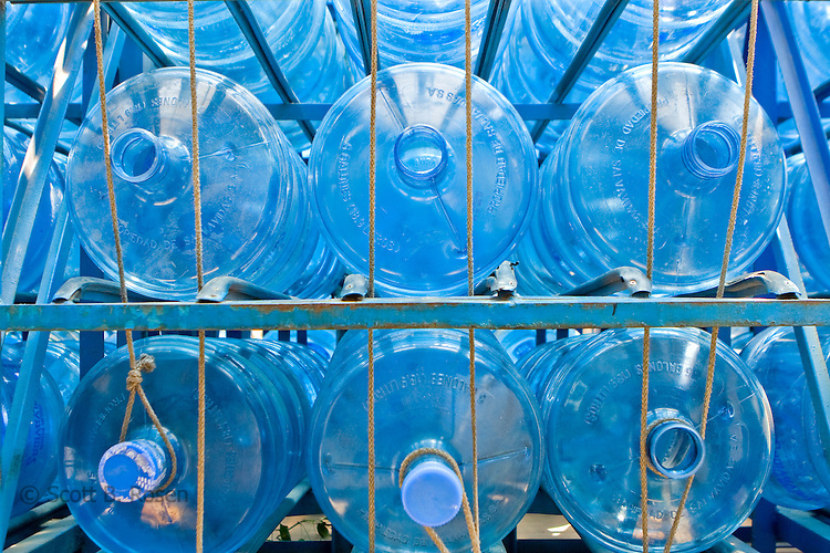 Rows of filled and empty filtered water jugs siting on the back of a delivery truck, Lake Atitlan, Guatemala