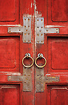 Red Doors 01 - Weathered red painted panelled wooden doors with metal door pull rings, Hue, Viet Nam.