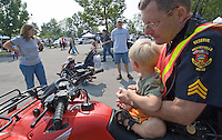 A family watches as a Westerville, Ohio, police officer gives their child a seat aboard an all terrain vehicle at the Cops and Kids Day at Hoff Woods Park.<br />