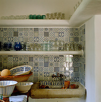 The walls of this whitewashed kitchen pantry are lined with blue and white tiles