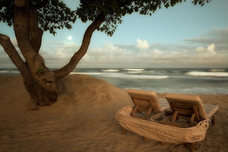Moon setting over ocean with beach chairs. Hawaii, The big Island.