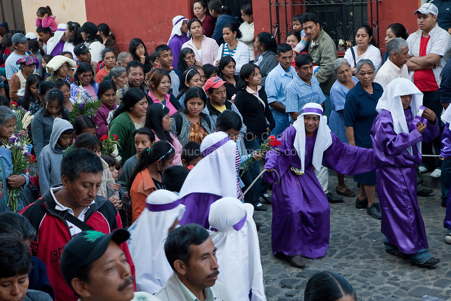 Antigua, Guatemala.  Spectators Following a Religious Procession during Holy Week, La Semana Santa.  Cucuruchos Holding the Rope Forming a Protective Zone Around the Float (Anda).