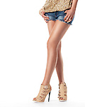 Closeup of sexy young woman legs wearing shorts and high heel shoes isolated on white background Image © MaximImages, License at https://www.maximimages.com