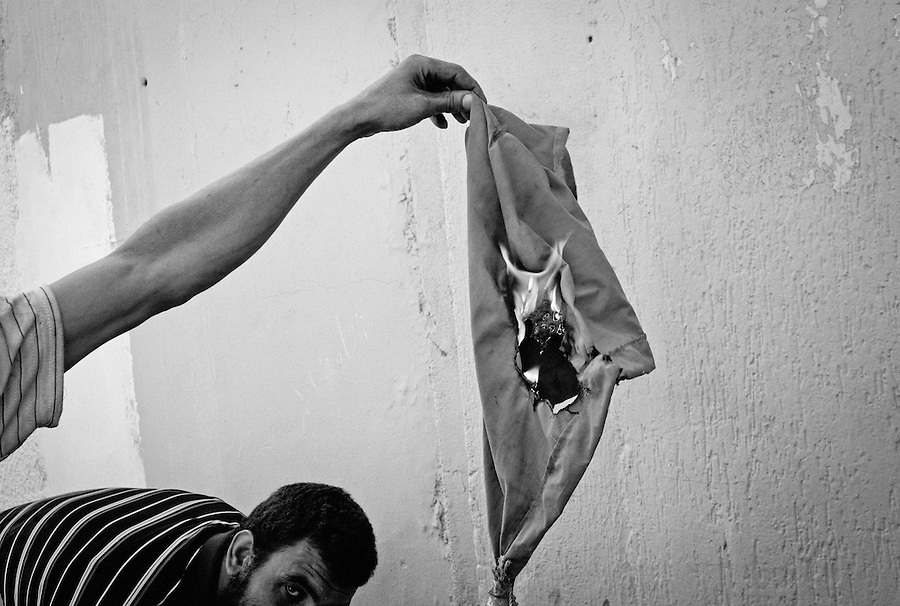 Rebel fighters burn Gaddafi flag in Tripoli, Libya