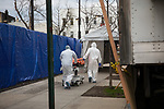 Healthcare workers transport the body of COVID-19 victim to a refrigerated trailer used as a temporary morgue outside of Wyckoff Heights Medical Center in the Brooklyn borough of New York City on April 5, 2020.  Photograph by Michael Nagle