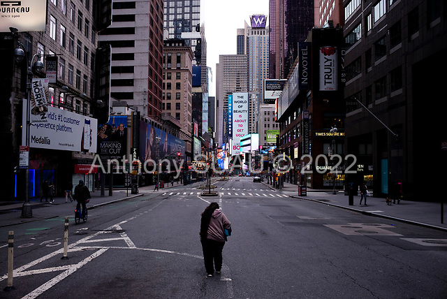 """New York, New York<br /> April 4, 2020<br /> <br /> The 7th Avenue in mid-town Manhattan just north of Times Square.<br /> <br /> The coronavirus has transformed urban architectural spaces with fear of proximity. Not entirely void of humanity, social distancing, within expansive city environments has created a landscape of aggrandizing physical structures and expanding spaces while diminishing the scale of humans. Face masks enhance the anonymity of """"the person"""", reducing them to a figure or an uninterrupted shadow falling on a surface."""
