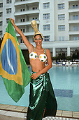 Rio de Janeiro, Brazil. Female model in football bikini and World Cup headdress holding a Brazilian flag beside a swimming pool.