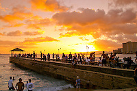 People gather to see another beautiful Hawaiian sunset from the pier at the Kuhio Beach park next to Waikiki Beach,Oahu.