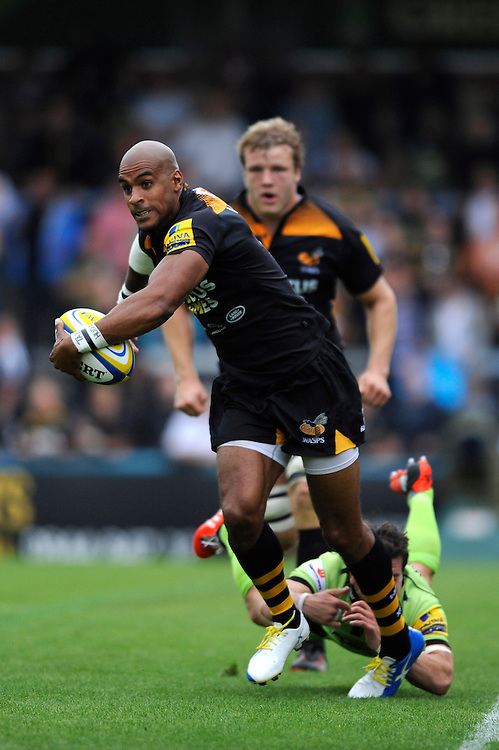 Tom Varndell of Wasps runs through the tackle of Lee Dickson of Northampton Saints during the Premiership Rugby Round 2 match between Wasps and Northampton Saints at Adams Park on Sunday 14th September 2014 (Photo by Rob Munro)