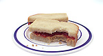 plate with peanut butter and jelly sandwich on white bread with one bite taken on shadowless white background