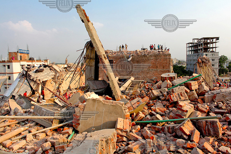 Rescue teams and civilian helpers search for survivors on one of the floors of the collapsed Rana Plaza complex in Savar.The 8 storey Rana Plaza complex, which housed a number of garment factories employing over 3,000 workers, collapsed on 24 April 2013. By 29 April, at least 380 were known to have died while hundreds remained missing. Workers who were worried about going to work in the building when they noticed cracks in the walls were told not to worry by the building's owner, Mohammed Sohel Rana, who is a member of the ruling Awami League's youth front. He fled his home and tried to escape to neighbouring India after the building collapsed but was caught by police and brought back to Dhaka. Some of the factories working in the Rana Plaza building produce cheap clothes for various European retailers including Primark in the UK and Mango, a Spanish label. The final death toll was 1,127. /Felix Features