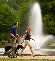People walk past a fountain at Freedom Park in the Myers Park neighborhood in Charlotte, NC. Myers Park is one of the premier neighborhoods in North America and known for its large canopy of trees.