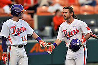 Designated hitter Reed Rohlman (26) of the Clemson University Tigers, right, is congratulated by Adam Renwick (11) after scoring a run in the fourth inning  of a game against the Wofford College Terriers on Tuesday, March 1, 2016, at Doug Kingsmore Stadium in Clemson, South Carolina. Clemson won, 7-0. (Tom Priddy/Four Seam Images)