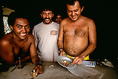 Amazon, Para state, Brazil. Illegal garimpeiro gold miners putting gold nuggets into a plastic bag after weighing them; Maria Bonita mine.