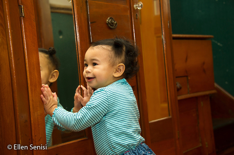 MR / Schenectady, NY. Toddler in early walking stage (1 year and 2 months old, African-American and Caucasian) Toddler in early walking stage smiles as she glances up; supporting herself on furniture while standing. MR: Dal4. ID: AM-HD. © Ellen B. Senisi