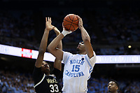 CHAPEL HILL, NC - MARCH 03: Garrison Brooks #15 of the University of North Carolina shoots over Ody Oguama #33 of Wake Forest University during a game between Wake Forest and North Carolina at Dean E. Smith Center on March 03, 2020 in Chapel Hill, North Carolina.