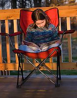 A young girls reads from a book sitting in a chair on a wooden deck in the late afternoon sunset on a spring day.<br />