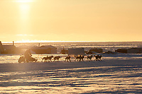 Ketil Reitan runs past fish camps at sunset on the trail heading toward the finish at Nome on Wednesday March 14th during the 2018 Iditarod Sled Dog Race.  <br /> <br /> Photo by Jeff Schultz/SchultzPhoto.com  (C) 2018  ALL RIGHTS RESERVED