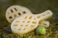 Two Pasta Tennic Rackets on Pesto Sauce with a fresh Green Pea as a ball
