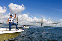 A fisherman reacts to a small catch in the Cooper River as the Cooper River Bridge is in the background in Charleston, SC.