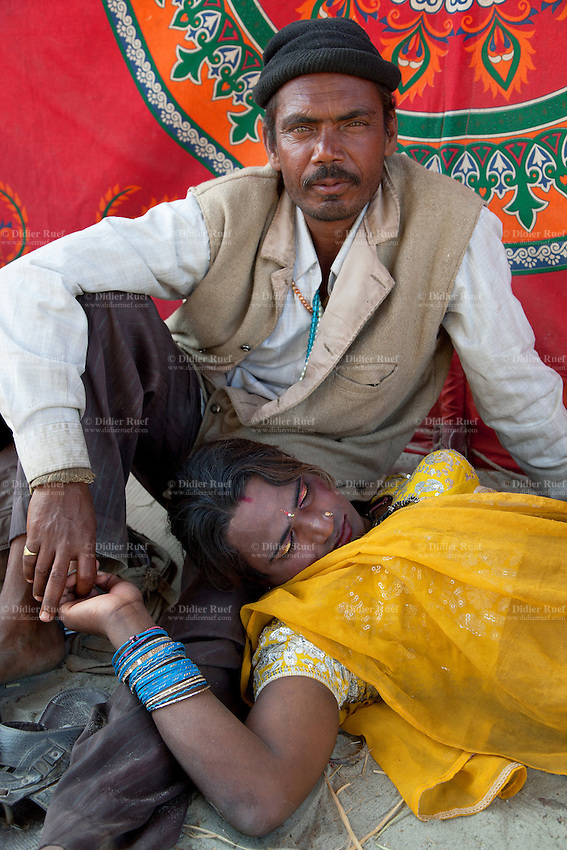 """India. Uttar Pradesh state. Allahabad. Maha Kumbh Mela. An Indian Hindu couple in Sangam. The woman wearing a yellow saree is an Hijra. She is asleep with her head laid on her man's leg. Hijras /eunuchs are physiological males who have feminine gender identity, adopt feminine gender roles, and wear women's clothing. The word hijra is a Hindustani word, derived from the Arabic root hjr in its sense of """"leaving one's tribe,"""" and has been borrowed into Hindi. The Indian usage has traditionally been translated into English as """"eunuch"""" or """"hermaphrodite,"""" where """"the irregularity of the male genitalia is central to the definition."""" However, in general hijras are born with typically male physiology, only a few having been born with male intersex variations. Since the late 20th century, some hijra activists and Western non-government organizations (NGOs) have been lobbying for official recognition of the hijra as a kind of """"third sex"""" or """"third gender,"""" as neither man nor woman. The Kumbh Mela, believed to be the largest religious gathering is held every 12 years on the banks of the 'Sangam'- the confluence of the holy rivers Ganga, Yamuna and the mythical Saraswati. The Maha (great) Kumbh Mela, which comes after 12 Purna Kumbh Mela, or 144 years, is always held at Allahabad. Uttar Pradesh (abbreviated U.P.) is a state located in northern India. 13.02.13 © 2013 Didier Ruef"""