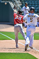 Tommy Medica (24) of the El Paso Chihuahuas reaches for the throw as Ryan Jackson (5) of the Salt Lake Bees hustles to first base at Smith's Ballpark on July 26, 2015 in Salt Lake City, Utah. El Paso defeated Salt Lake 6-3 in 10 innings.  (Stephen Smith/Four Seam Images)