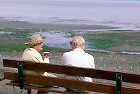 "A Senior Couple sitting on a Bench beside the Pacific Ocean at Qualicum Beach, in the ""Oceanside Region"" of Vancouver Island, British Columbia, Canada (No Model Release Available)"