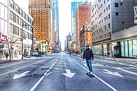 New York, New York City. New Yorkers are told to stay home during the corona virus, (COVID-19) so New York has become eerily empty. A man skateboards down 8th avenue,  a street  devoid of all cars and people in the Theatre District.