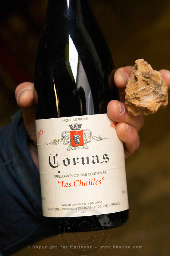 Alberic Mazoyer showing in his hand a bottle of Cornas les Chailles and a stone from the soil type 'Chailles' that has given its name to the wine. Alain Voge, Cornas, Ardeche, Ardèche, France, Europe