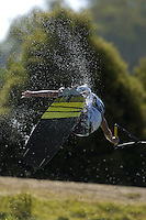 A male wakeboarder preforms a trick in the air.