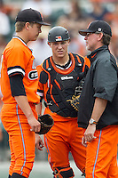 Oklahoma State Cowboys starting pitcher Tyler Buffett #37 talks with catcher Gage Green #17 and pitching coach Rob Walton #10 during the NCAA baseball game against the Texas Longhorns on April 26, 2014 at UFCU Disch–Falk Field in Austin, Texas. The Cowboys defeated the Longhorns 2-1. (Andrew Woolley/Four Seam Images)