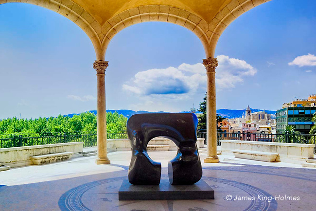 A black marble sculpture by the English artist Henry Moore stands on a covered terrace of the Palau March (March Palace) museum in Palma de Mallorca where the March Foundation's collection of modern sculpture can be seen. The Palace overlooks the city of Palma. A black marble sculpture, titled 'Square Form with cut',  by the English artist Henry Moore stands on a covered terrace of the Palau March (March Palace) museum in Palma de Mallorca where the March Foundation's collection of modern sculpture can be seen. The Palace overlooks the city of Palma.