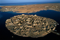 The ancient port of Suakin.Sudan has long been ruled by a small circle of wealthy northerners, who, because of their Muslim faith and Arabized culture, consider themselves Arab instead of African.  Islam and Arab culture came to Sudan through trading centers like the ruined Red Sea port of Suakin.  By the 14th century the religion had been widely adopted by northern merchants and kings.  ..Story Summary:.Sudan, the largest country in Africa, hosts a civil war between the Islamic North and the African South that has the highest casualty rate of any war since World War II...Two and a half million people have been killed in this insidious conflict.  It drags on because Southerners have no voice, and the Northerners have engineered ÒThe Perfect WarÓ where none of their people are killed...The North forces people out of the South by bombing them, burning their crops, and harassing them with gun ships. They abduct their children and draft them to fight with the Northern armyÑforcing southerners to fight their own brothers...This story is particularly interesting now because there is a small window for peace in a civil war that has been dragging on since the end of colonial rule.  The war has always been about tribal issues and ideologyÉ but more than that, it is about resources.  This clash over resources may bring peace.  The North controls the pipeline and the only port, and the South controls the land...The story of Sudan has always been the continual transference of wealth from the resources of the south to the elite few who live in the deserts of the north.  And the sucking sound in the middle of the country is from the corrupt government in northern Khartoum..