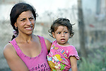 A woman holds her daughter in the largely Roma neighborhood of Gorno Ezerovo, part of the Bulgarian city of Burgas. Residents here don't self-identify much as Roma, because of the negative connotations associated with the word, so many refer to themselves as a Turkish-speaking minority.