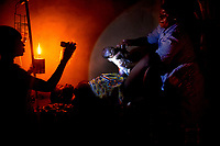 A woman uses a torch and an oil lamp to illuminate the room as midwife Raïssa Godjo helps Dossou Mariette give birth in a village that is off the electricity grid.