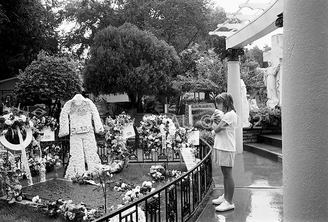 "Memphis, Tennessee<br /> USA<br /> August 14, 2002<br /> <br /> A young girl clings to her teddy bear at the grave of Elvis Presley in Graceland during ""Elvis Week"" marking the 25th anniversary of the King's death."