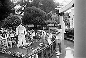 """Memphis, Tennessee<br /> USA<br /> August 14, 2002<br /> <br /> A young girl clings to her teddy bear at the grave of Elvis Presley in Graceland during """"Elvis Week"""" marking the 25th anniversary of the King's death."""