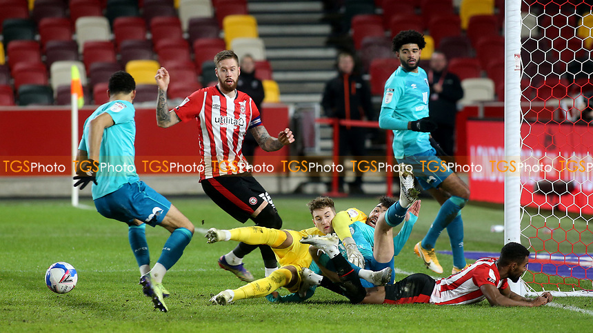 Brentford goalkeeper, David Raya is on the ground with AFC Bournemouth's David Brooks as the ball bounces  away to safety during Brentford vs AFC Bournemouth, Sky Bet EFL Championship Football at the Brentford Community Stadium on 30th December 2020