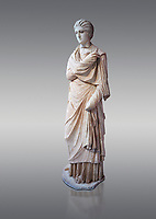 Statue of a female inj the Small Herculaneum Style, Athens Archaeological Museum, Cat no 242. Pentelic marble. Against grey<br /> <br /> Copy of earlier famous Greek statue dated 300 BC. The women is depicted wearing a full length chiton and a himation that covers her entire body.