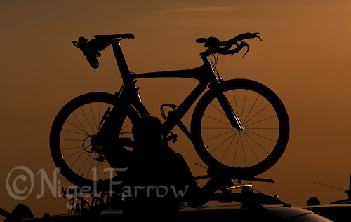 16 MAY 2010 - LYDD, GBR - A competitor takes his bike off his roof rack as he prepares for theThe Marshman Triathlons .(PHOTO (C) NIGEL FARROW)
