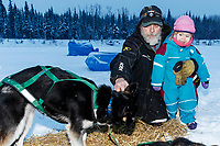 Long-time lead Nikolai checker John Runkle shows his 2-year old grandaughter Anavay Runkle a pair of Ryan Redington dogs at the Nikolai checkpoint during the 2018 Iditarod race on Tuesday March 06, 2018. <br /> <br /> Photo by Jeff Schultz/SchultzPhoto.com  (C) 2018  ALL RIGHTS RESERVED