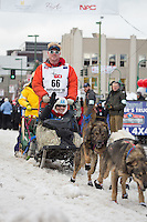 Steve Watkins and team leave the ceremonial start line with an Iditarider at 4th Avenue and D street in downtown Anchorage, Alaska during the 2015 Iditarod race. Photo by Jim Kohl/IditarodPhotos.com