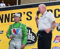 Jul, 22, 2012; Morrison, CO, USA: NHRA funny car driver Jack Beckman (left) alongside NHRA announcer Alan Reinhart after winning the Mile High Nationals at Bandimere Speedway. Mandatory Credit: Mark J. Rebilas-