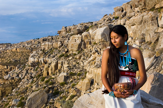 Traditional Hopi girl, Povi Lomayauma 16 year old teenager, dressed in traditionally woven cotton dress holds a traditional fired clay pottery bowl while posing on the First Mesa near Polacca Arizona. Povi's homelands are ancient rock canyons that offered protection for her ancestors.
