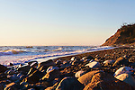 Sunset on beach at Fort Ebey State Park.  Whibey Island, WA.  Boulders and surf.