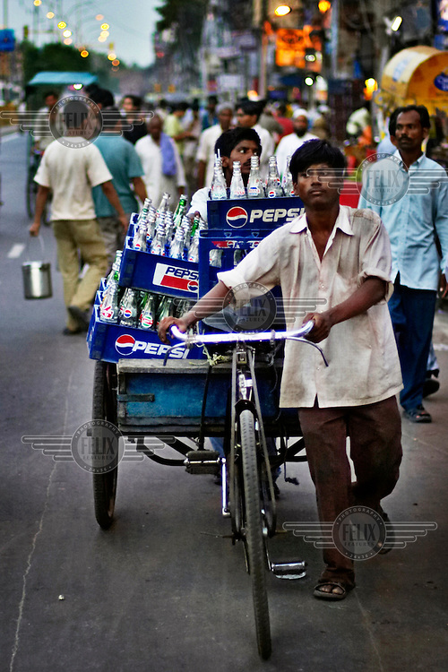 A man pushes a bicycle rickshaw loaded with crates of empty Pepsi glass bottles in New Delhi's old city.
