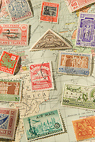 An Assortment of Colorful Vintage Postage Stamps from Various Countries Around the World against a 1929 Map of the World